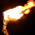 hand holds a flaming torch aloft against a night sky