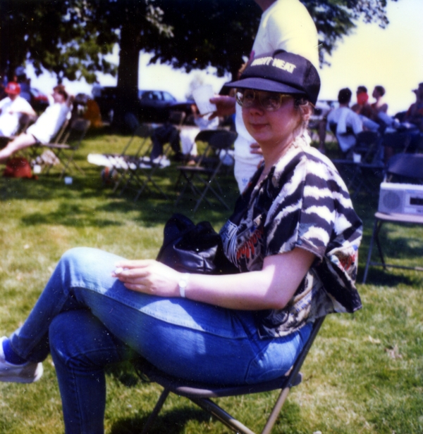 Laurel sitting on a folding chair at a back yard picnic, wearing a Night Heat baseball cap, circa 1980s