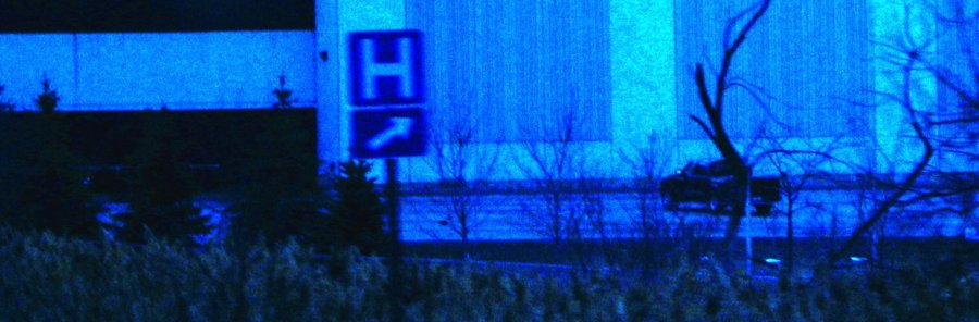 Blue hospital sign with an arrowat the side of the highway