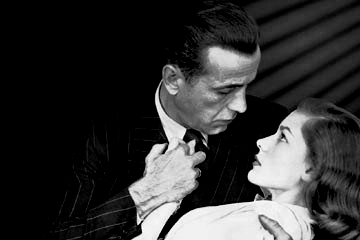 "Black and white image of Humphrey Bogart and Lauren Bacall in a publicity still Wikipedia called ""the big clinch"""