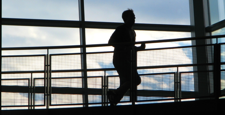 Runner silhouetted on the indoor running track