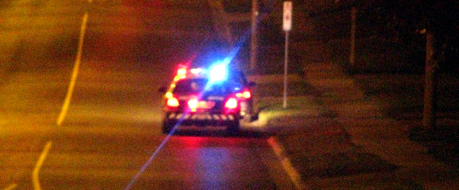 Red and blue lights flashing as a police car is parked behind the car it has pulled over on a lonely road at night