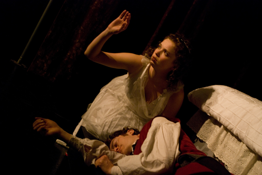 Romeo lays dead on the floor as Juliet holds her hand up to the light